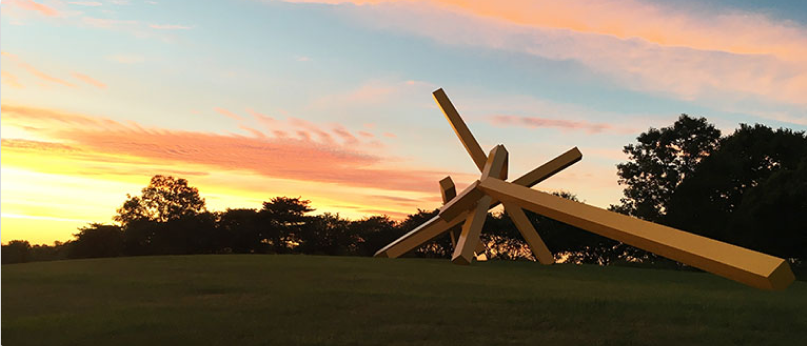 A large yellow steel sculpture titled 'Illinois Landscape No. 5' at sunset