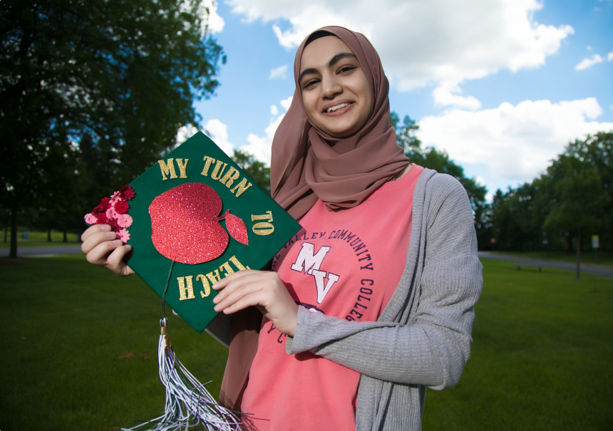 Rama Diab, current student at GSU, holding a graduation cap that says, 'my turn to teach'