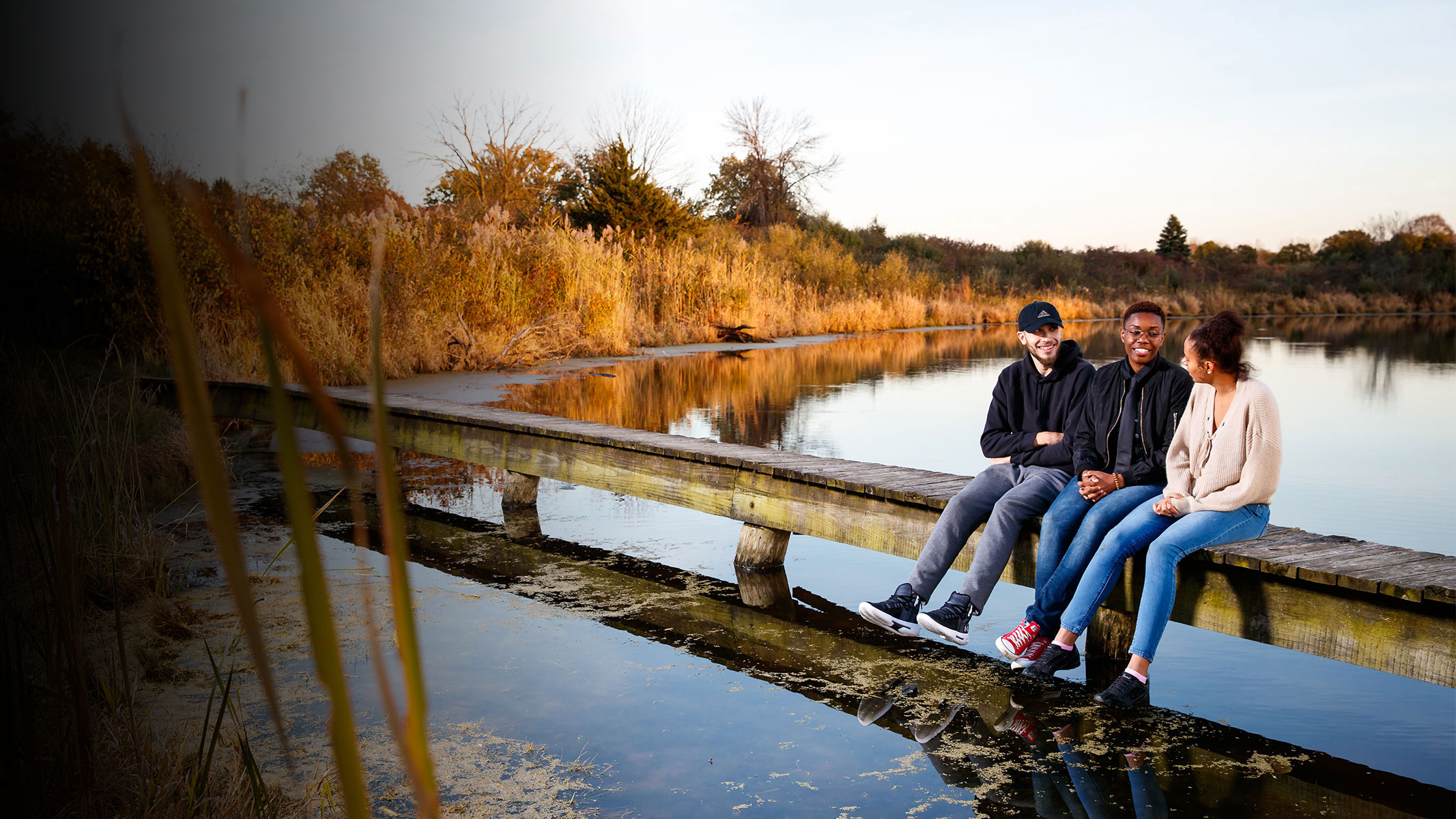 Three students sitting on the dock by the lake