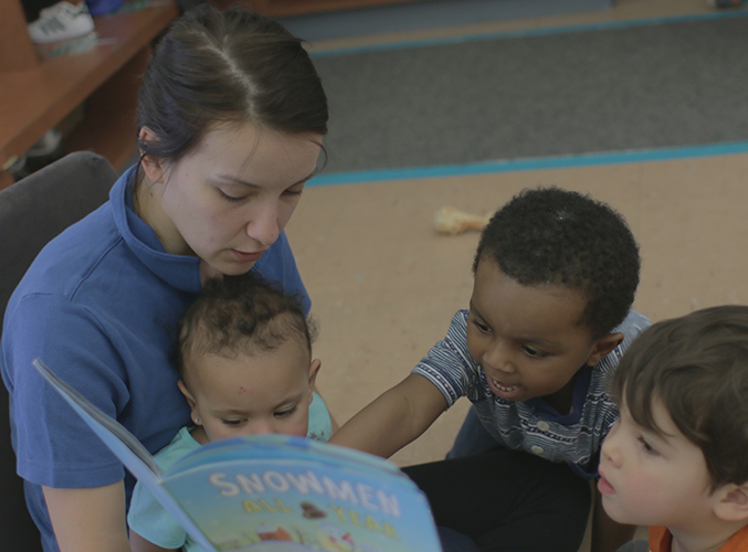 FDC staff member reading book to children