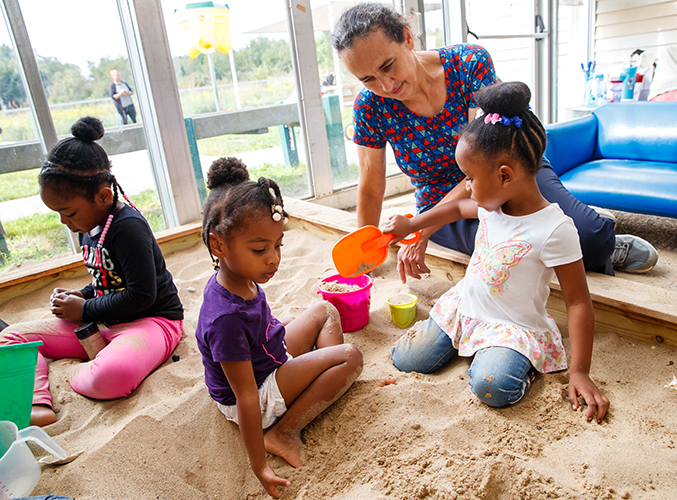 FDC staff member playing with children in sandbox