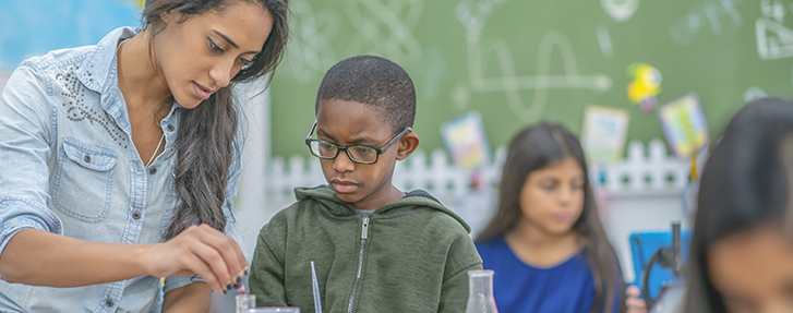 Teacher assisting student with chemistry experiment
