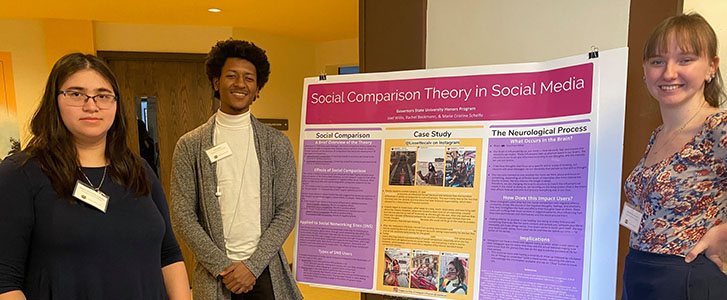 Students smiling next to their presentation poster board on Social Comparison Theory in Social Media