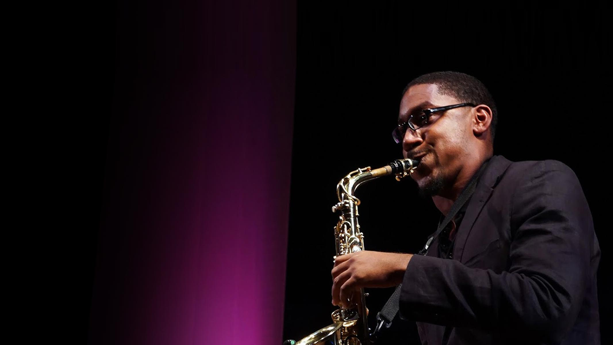A Family and Friends Talent Showcase with a GSU student playing a saxophone