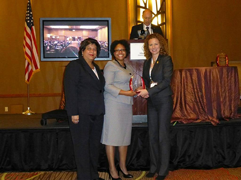 L-R Aida Martinez and Roshaunda Ross receive the Institutional Excellence for Students in Transition Award from Jennifer Keup, the Director of the National Resource Center for the First-Year Experience and Students in Transition during the FYE/Students in Transition Conference ceremony in Denver.