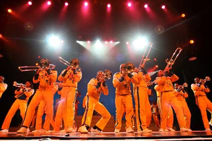 Photo from stage production of DRUMLine Live showing several trombone players wearing band uniforms.